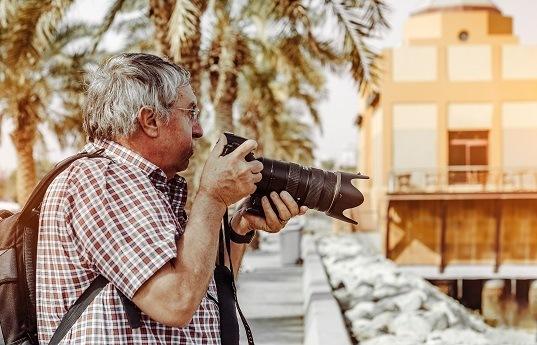 Senior im Urlaub mit Kamera